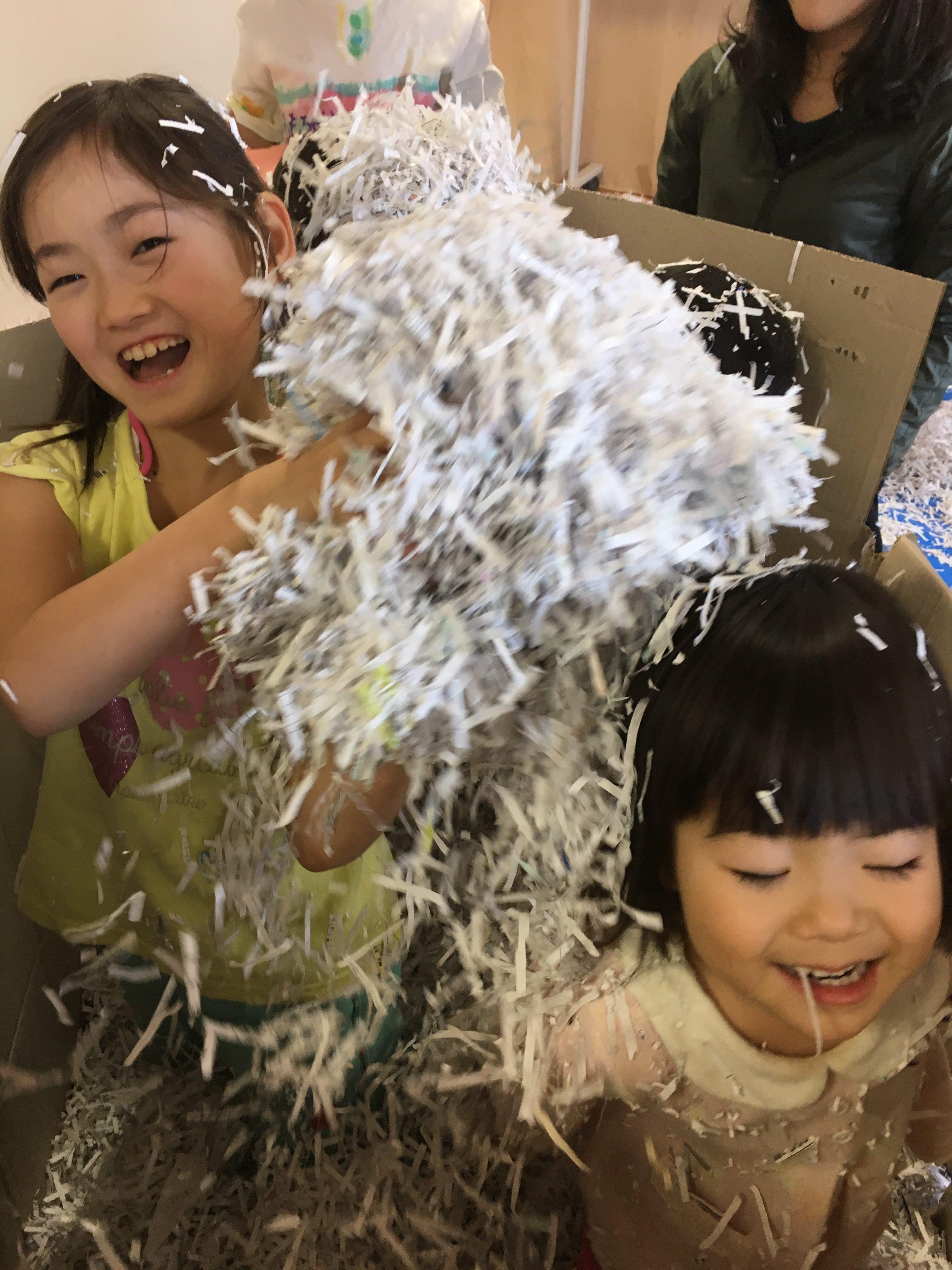 子どものアートセラピー教室でシュレッダーで裁断した紙で遊ぶ子どもたちの様子